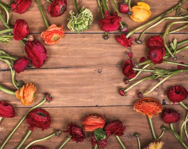 木製のテーブルに赤い花のラナンキュリュスの花束