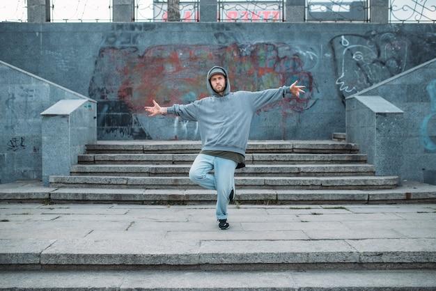 Рэп-исполнитель позирует на ступеньках, уличные танцы. современный городской танцевальный стиль. мужчина танцор