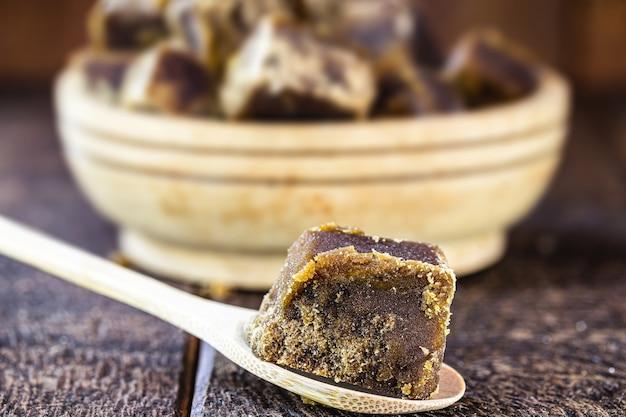 木のスプーンでバラバラにしたラパドゥラキャンディー、サトウキビ糖蜜から作られたキャンディー