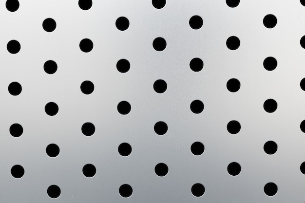 Rapid black dot pattern on gray background, round holes texture on perforated metal panel surface.