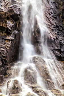 The rapid stream of water falling from a cliff