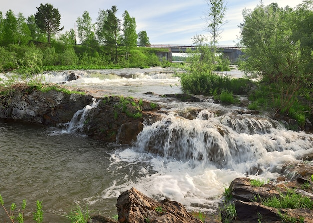 白い泡の山川の水の流れのスエンガ川の石の土手に急流
