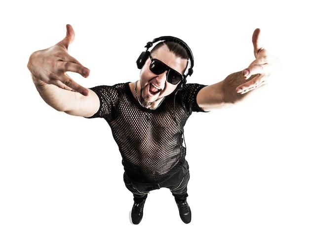 Рэпер в стильной футболке с наушниками и с поднятыми руками на белом
