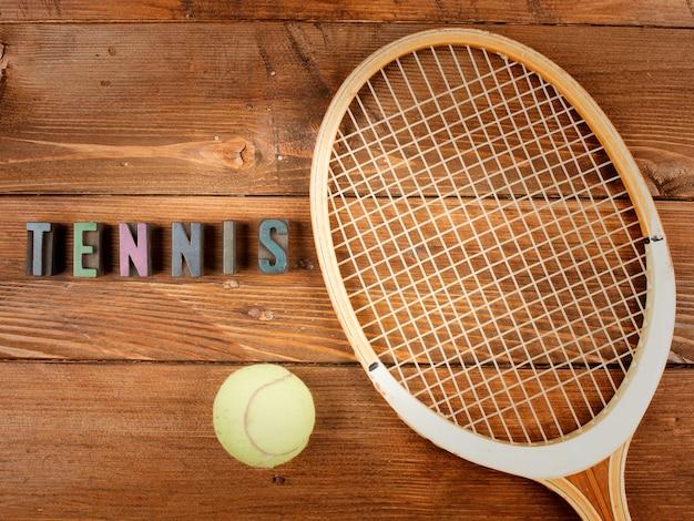 Raquet and ball in wood and word tennis in letterpress type