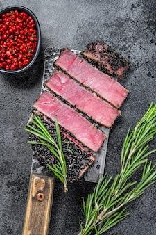 肉切り包丁の珍しいアヒマグロステーキスライス。黒の背景。上面図。