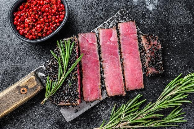 Редкие кусочки стейка из тунца ахи на ноже для мяса.