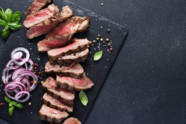 양파와 바질을 곁들인 돌판에 희귀 쇠고기 조각. 검은색 바탕에 미디엄 레어 쇠고기 스테이크.