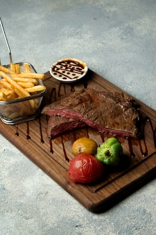 Rare cooked steak served with fries, grilled vegetables and sauce