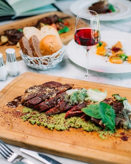 Rare cooked steak slices served with mashed avocado walnut lettuce spinach red wine