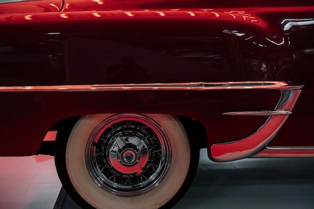 白いタイルの上に立っている赤いレトロな車の珍しい部分