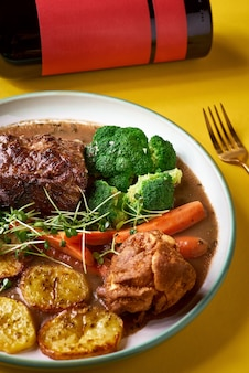 オーガニックの根菜を使った珍しいローストビーフの食事と、伝統的なヨークシャープディングのソース煮込み野菜。