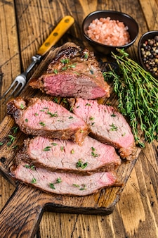 Редкие ломтики жареной говяжьей вырезки на деревянной разделочной доске