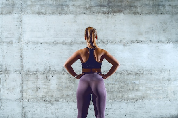 Rare view of fit muscular caucasian sportswoman in sportswear with ponytail standing with hands on hips.