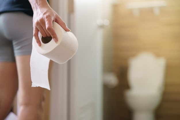 Rare view of man holding toilet paper roll in the front of toilet.