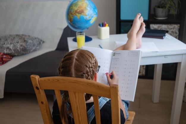 Редкий вид кавказской рыжей девушки в очках учится дома, делает домашнее задание. пишу. умник. концепция дистанционного образования. карантин. снова в школу концепции.