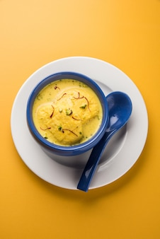 Ras malai 또는 rossomalai는 인도 벵골의 디저트입니다. 사프란이나 케사르&피스타치오 토핑을 얹은 크러스트가 없는 진한 치즈케이크입니다. 나무 또는 화려한 배경 위에 그릇에 제공