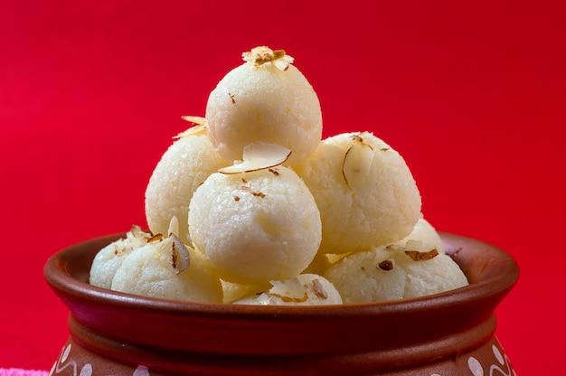 Индийский сладкий или десерт - rasgulla, знаменитый бенгальский сладкий в глиняной миске с салфеткой на красный