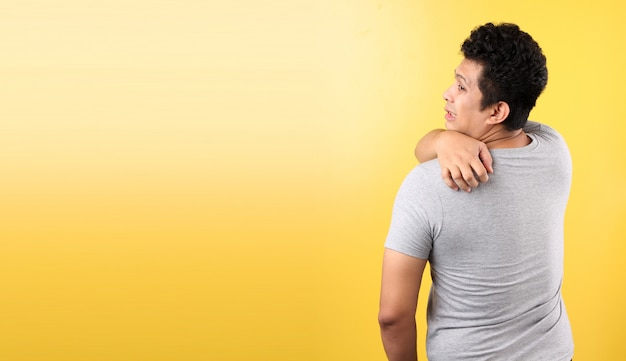 健康上の問題、皮膚病。黄色い壁にアレルギーrash.onでかゆみ背中を掻く若いアジア人。
