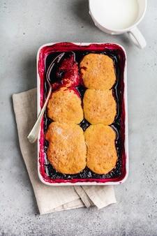 ラズベリーと黒スグリのコブラーとラズベリーアイスクリームをグラタン皿に。自家製フルーツパイペストリー。灰色のヴィンテージの背景。上面図。