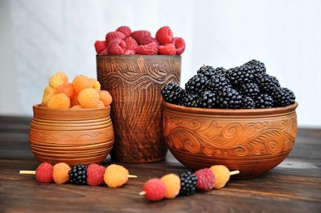Малина и ежевика красные, желтые и черные в глиняной посуде