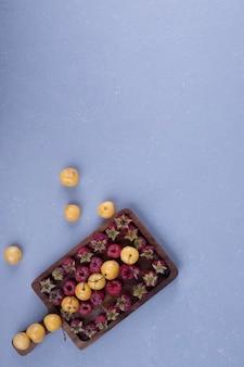 Малина и вишня на деревянном блюде на нижней стороне