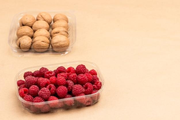Малина и грецкие орехи в пластиковых контейнерах