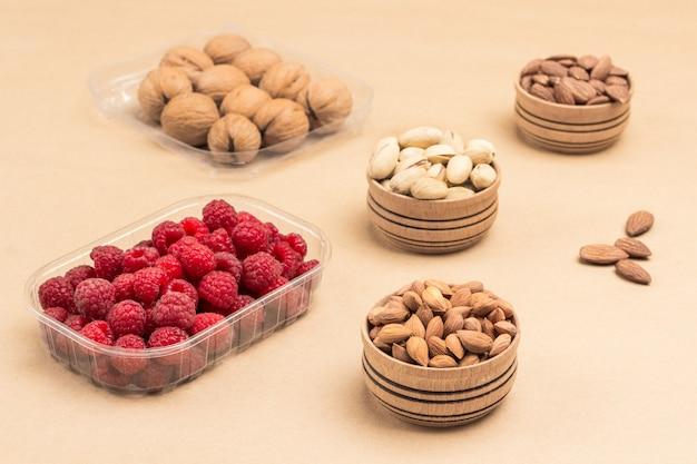 Малина и грецкие орехи в пластиковых контейнерах.
