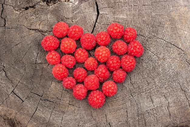 Raspberries berry heart shape on old cracked stump, concept love raspberries summer