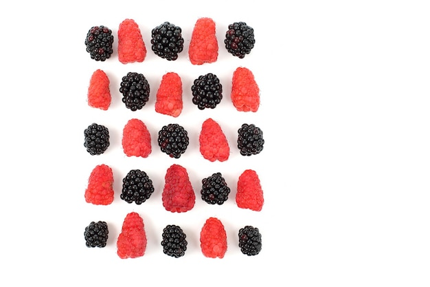 Raspberries and blackberries are laid out in a square on a white background