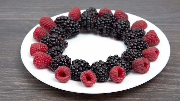 Raspberries and blackberries on a white plate. vitamin and diet food