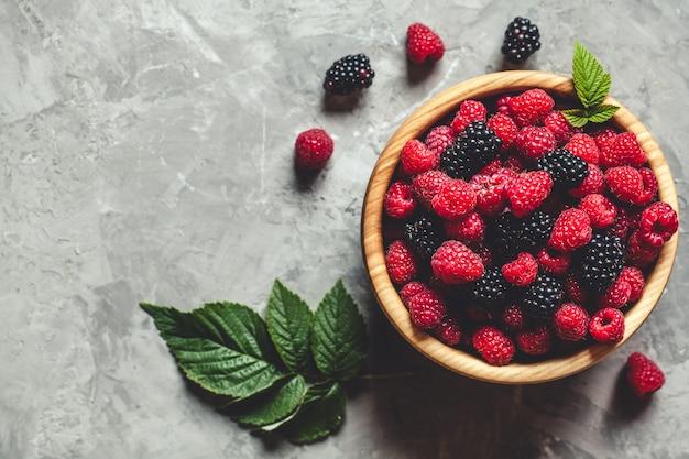 Raspberries and blackberries in wood bowl on gray table, vintage