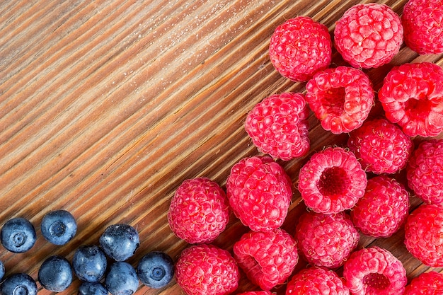 Raspberries and blueberries on a wooden background