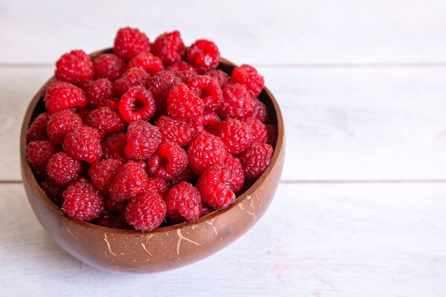 Raspberries in a coconut shell bowl on a white wooden table