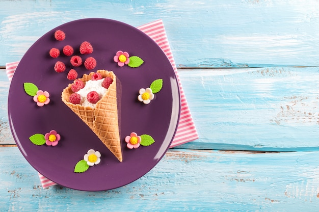 Raspberries and cottage cheese in the ice cream cone for children's breakfast