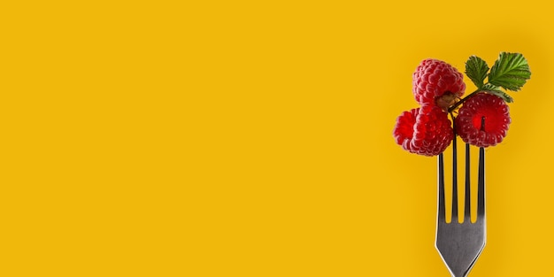 Raspberries on fork against yellow background. healthy eating concept. summer food. trendy minimal style. natural organic products. healthy lifestyle. long wide banner. copy space for your design.