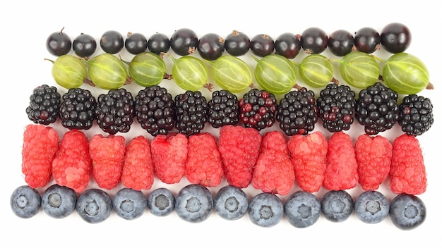 Raspberries, gooseberries, blackberries, currants and blueberries in rows on a white background. healthy fresh vegetables and food