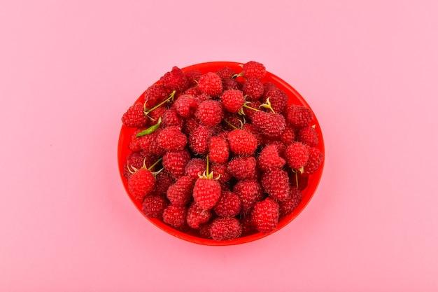 ピンク色の空間に赤い皿にラズベリー。ピンクのスペースに新鮮なラズベリーをボウルします。コピースペース。最小限のコンセプト。ハードライト。