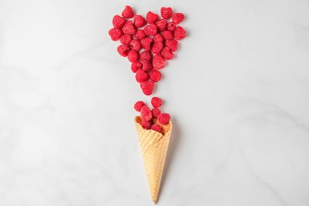 Малина в вафельном рожке мороженого и сердце из ягод на белом мраморе. свежие летние ягоды