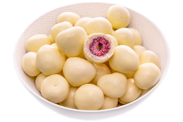 Малина в белом шоколаде в светлой тарелке на белом фоне. изолированные продукты