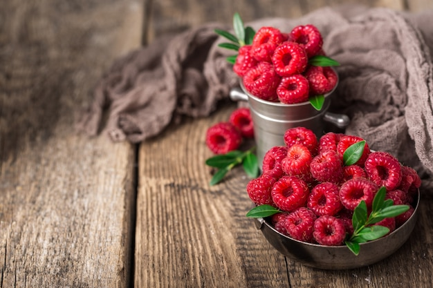 Raspberries in metal dishes on wooden table.