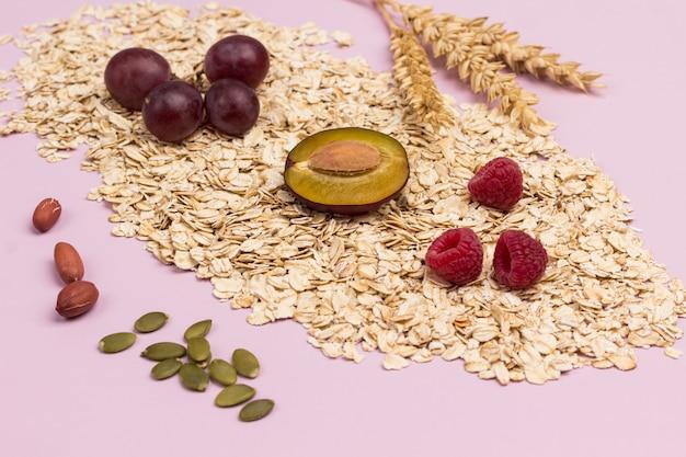 Малина, сливы и виноград на овсянке. семена тыквы и колоски пшеницы на столе. плоская планировка. розовый фон