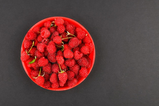 Raspberries in a red plate on a black background