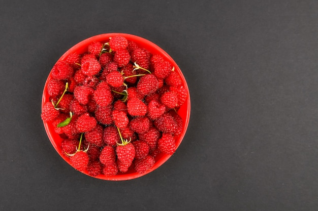 Raspberries in a red plate on a black space. bowl with fresh raspberries on a pink space. copy space. minimal concept. hard light.