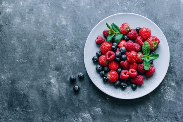 라스베리, 딸기, 민트와 블루 베리 어두운 구체적인 배경 상위 뷰 복사 공간에 회색 접시에 나뭇잎.