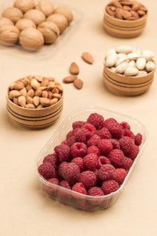 Raspberries and walnuts in plastic containers
