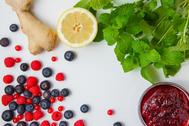 Raspberries with jam, blueberries, redcurrants, lemon, ginger, mint leaves top view on a white background