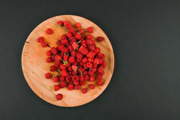 Raspberries on a wooden plate. on a black space close-up. wooden tray. view from above. place for writing. fresh raspberries on a dark stone space. close selective focus.