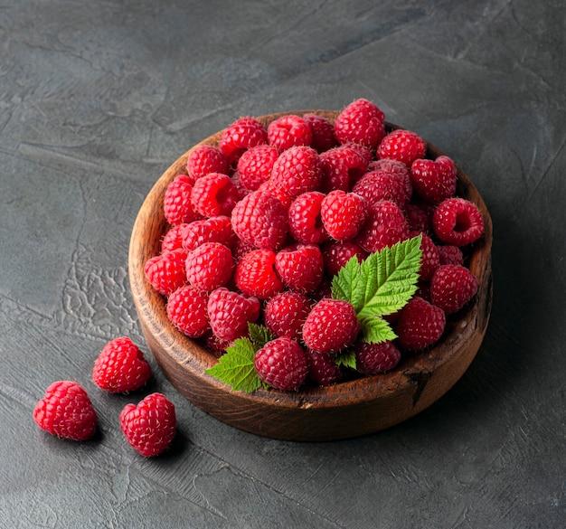 Raspberrries в деревянной тарелке на бетонном фоне.
