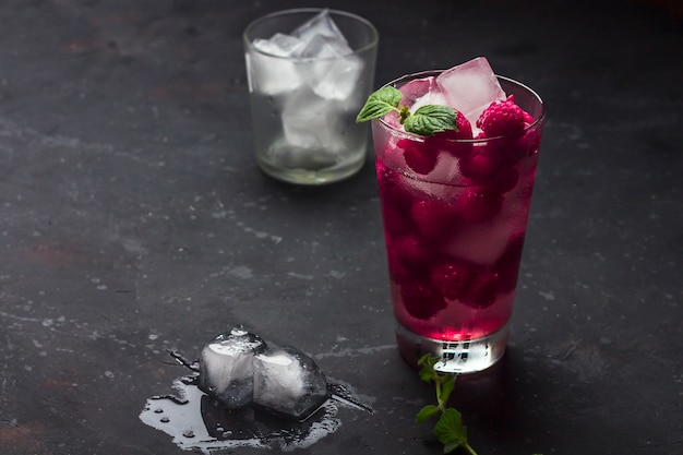 Raspberry alcoholic cocktail with liqueur, vodka, ice and mint on a dark background. raspberry mojito. refreshing cool drink, lemonade or ice tea in a glass, low key