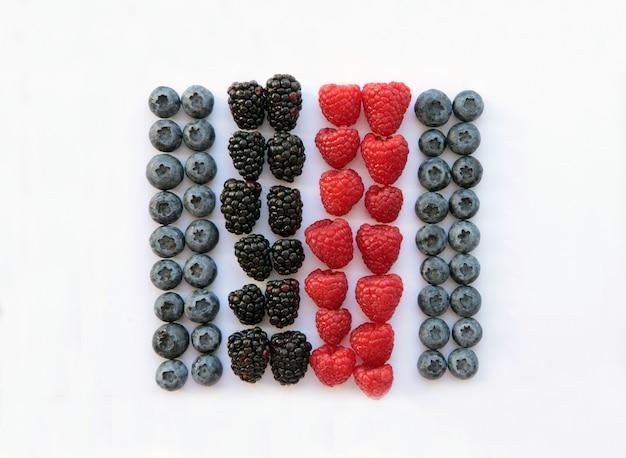 Малина и ежевика в квадрате изолированной белизны. концепция здоровых, органических продуктов питания и питания